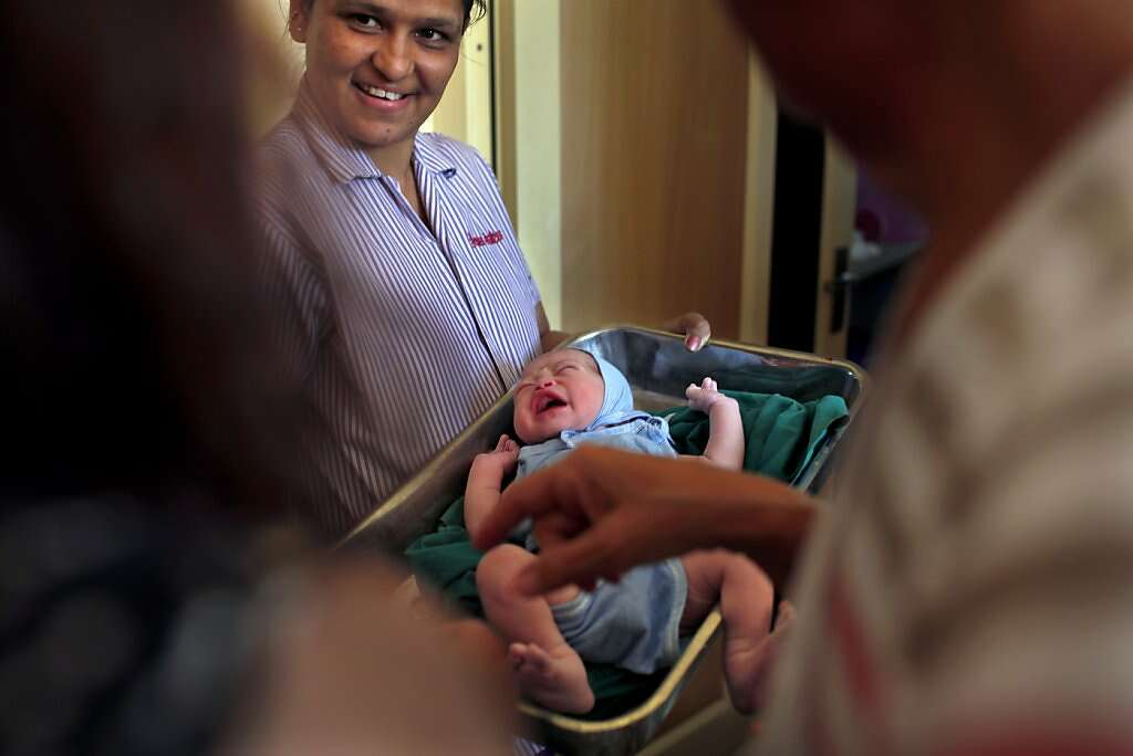 Hospital helper Hansa Harjan, center, shows baby Kyle Benito Kowalski to his mom Jennifer Benito-Kowalski, left, and grandmother Sue Kowalski for the first time at the Akanksha Infertility Clinic in Anand, India, Thursday, May 23, 2013. Photo: Nicole Fruge, The Chronicle