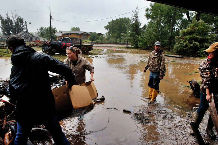 Local residents, from left, Levi Wolfe, Miranda Woodard, Tyler Sadar and Genevieve Marquez help salvage and clean property in an area inundated after days of flooding, in Hygiene, Colo. Photo: Brennan Linsley, STF / AP