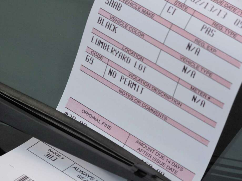 A parking ticket on the windshield of a car parked in the lumber yard lot without a permit. The parking commission recommended the purchase of a license plate reader in part to help patrol the lot. New Canaan, Conn. Photo: Tyler Woods