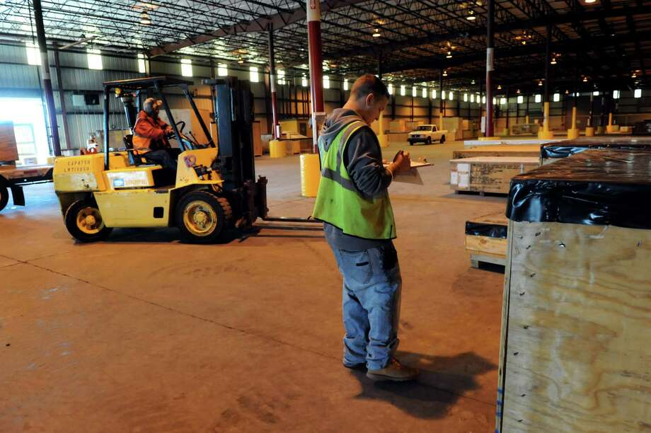 Clerk David Martino, center, keeps track of inventory as a longshoreman unloads turbine parts for General Electric on Tuesday, Sept. 17, 2013, at the Port of Albany in Albany, N.Y. (Cindy Schultz / Times Union) Photo: Cindy Schultz / 00023902A