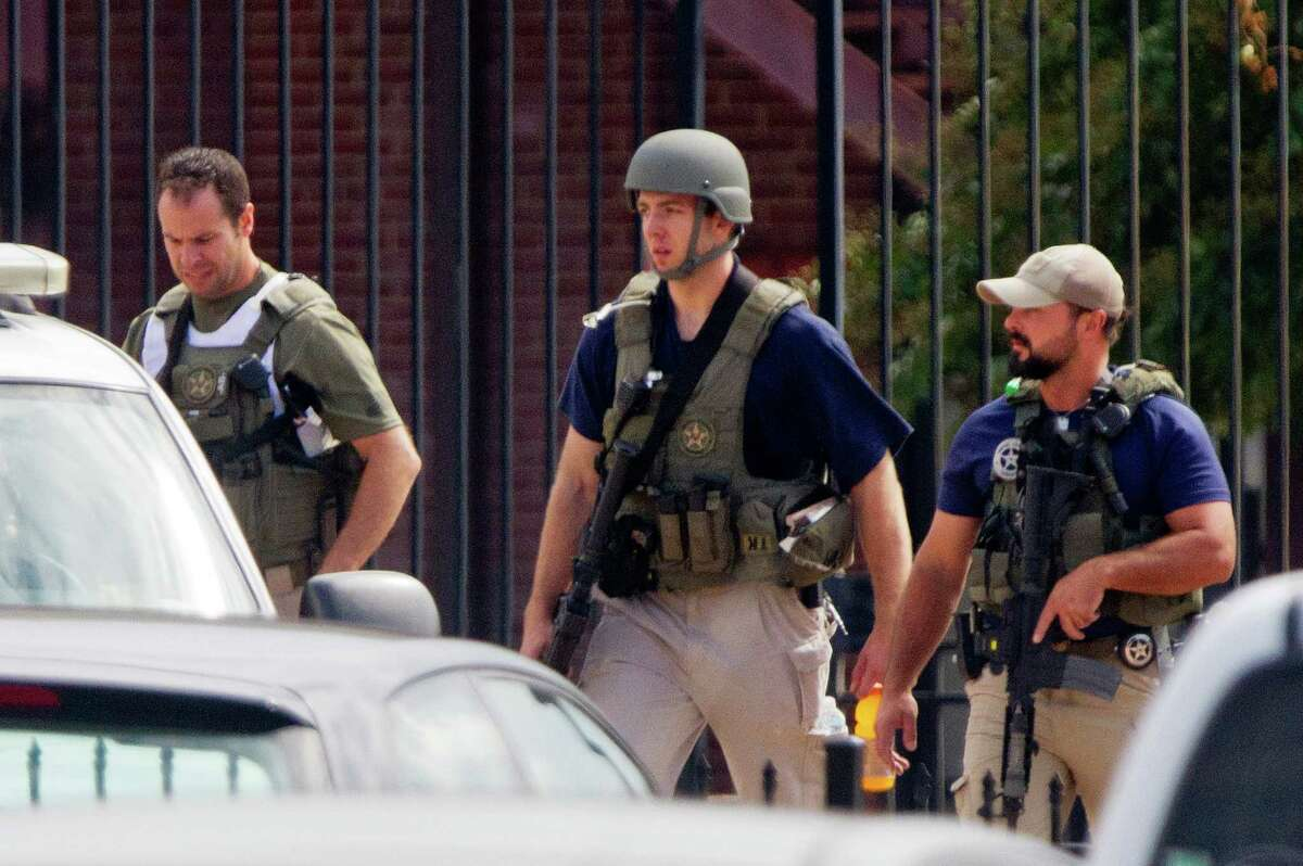 Armed U.S. Marshals leave the scene where a gunman was reported at the Washington Navy Yard in Washington, on Monday, Sept. 16, 2013. At least one gunman launched an attack inside the Washington Navy Yard, spraying gunfire on office workers in the cafeteria and in the hallways at the heavily secured military installation in the heart of the nation's capital, authorities said.