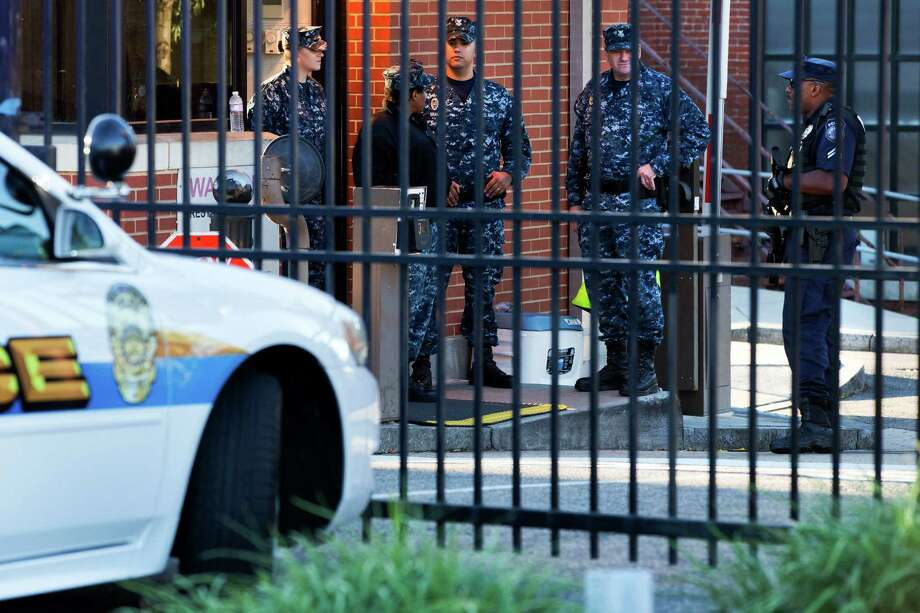 An officer who said he was with the Department of Defense, right, and members of the Navy, stand guard inside the gate of the closed Washington Navy Yard in Washington, on Tuesday, Sept. 17, 2013, the day after a gunman launched an attack inside the Washington Navy Yard. Photo: Jacquelyn Martin, STF / AP