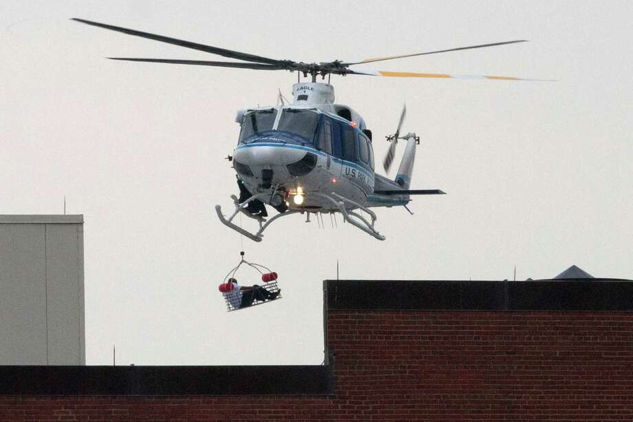 A U.S. Park Police helicopter removes a man in a basket from the Washington Navy Yard Monday, Sept. 16, 2013.    Earlier in the day, the U.S. Navy said it was searching for an active shooter at the Naval Sea Systems Command headquarters, where about 3,000 people work. Thirteen people were killed. Photo: Jacquelyn Martin