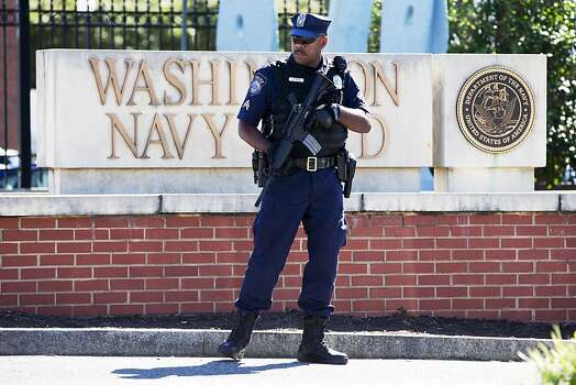 An armed officer who said he is with the Department of Defense, works near the gate at the Washington Navy Yard, closed to all but essential personnel. Photo: Jacquelyn Martin, Associated Press