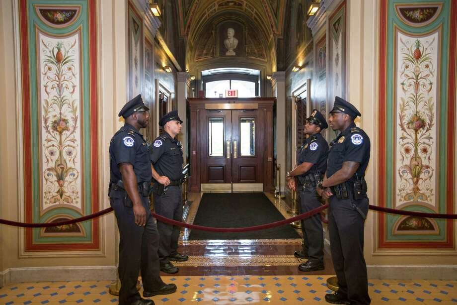 U.S. Capitol Police officers stand guard as doors are locked down inside the Capitol Building during the shooting at the Washington Navy Yard, Monday, Sept. 16, 2013, in Washington.  Photo: J. Scott Applewhite, STF / AP