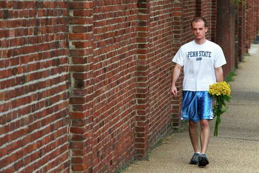 A man who would identify himself only as a Navy Yard employee walks past the wall encircling the Washington Navy Yard to leave a bouquet of flowers there in Washington, on Tuesday, Sept. 17, 2013. Photo: Jacquelyn Martin, STF / AP