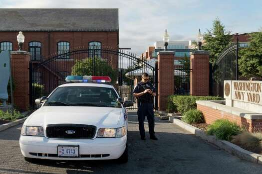 A police officer stands by a locked gate at the Washington Navy Yard, closed except to essential personnel, in Washington, on Tuesday, Sept. 17, 2013. The gate at right is open to allow ID checks of essential personnel.  Photo: Jacquelyn Martin, STF / AP