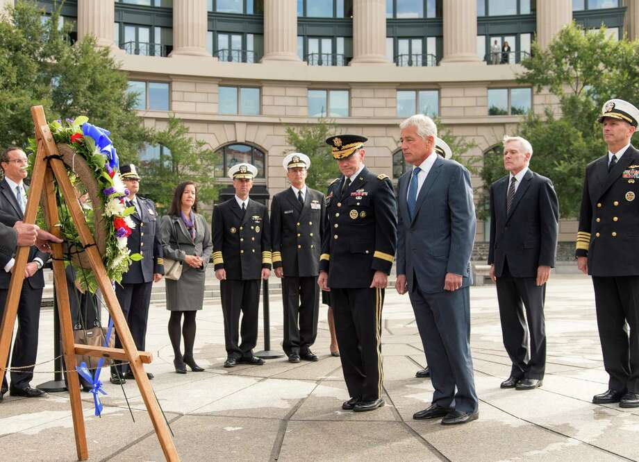 Defense Secretary Chuck Hagel, center right, and Joint Chiefs Chairman Gen. Martin Dempsey, center left, lead a delegation at the Navy Memorial in Washington to remember the victims of Monday's deadly shooting at the Washington Navy Yard. Photo: J. Scott Applewhite