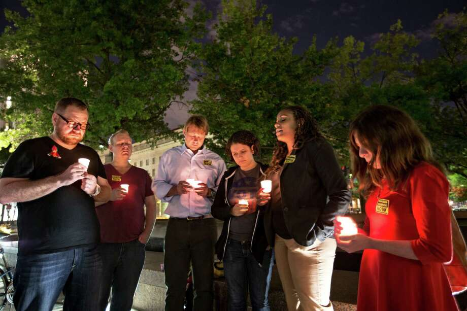 A small group holds a candle light vigil on Freedom Plaza to remember the victims of the shooting at the Washington Navy Yard, Monday. Photo: J. Scott Applewhite, STF / AP