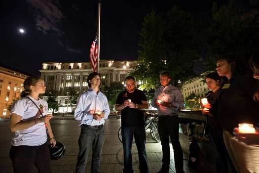 A small group holds a candle light vigil on Freedom Plaza to remember the victims of the shooting at the Washington Navy Yard, Monday, Sept. 16, 2013. Photo: J. Scott Applewhite