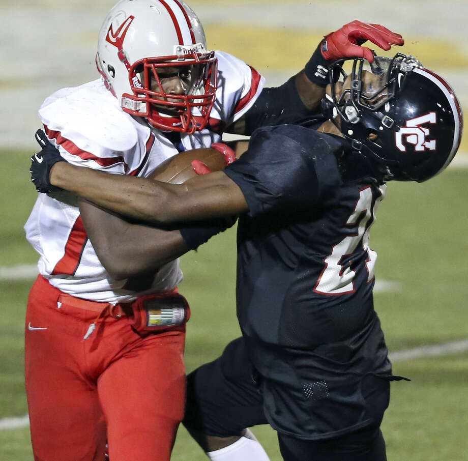 Judson's Jo'von Kyle looks for room to get around Churchill's Tyrin Foley Friday during second half action at Heroes Stadium. Judson prevailed, 28-6. Photo: San Antonio Express-News