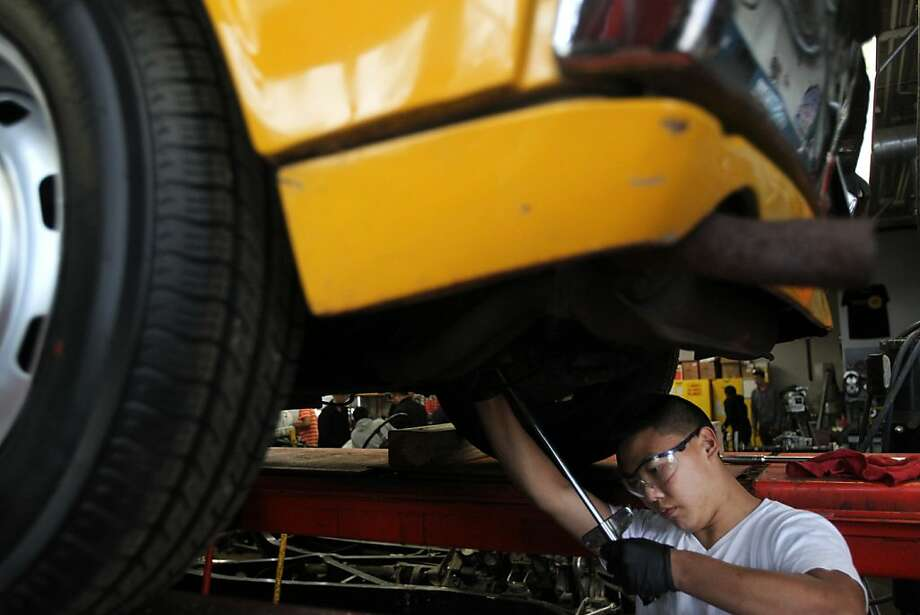 Derek Kwan, 17, tightens a bolt on a Porsche 914 during auto shop class at Washington High School. Photo: Leah Millis, The Chronicle