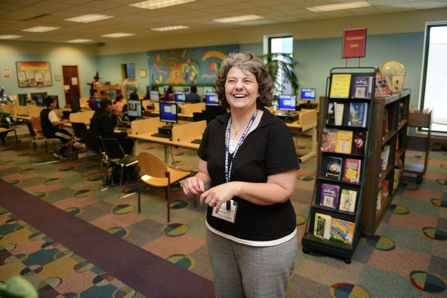 Danbury Public Library Director Michele Capozzella laughs in the children's section of the library in Danbury, Conn. on Tuesday, Sept. 17, 2013.  Capozzella will be stepping down from her position as library director at the beginning of October. Photo: Tyler Sizemore / The News-Times