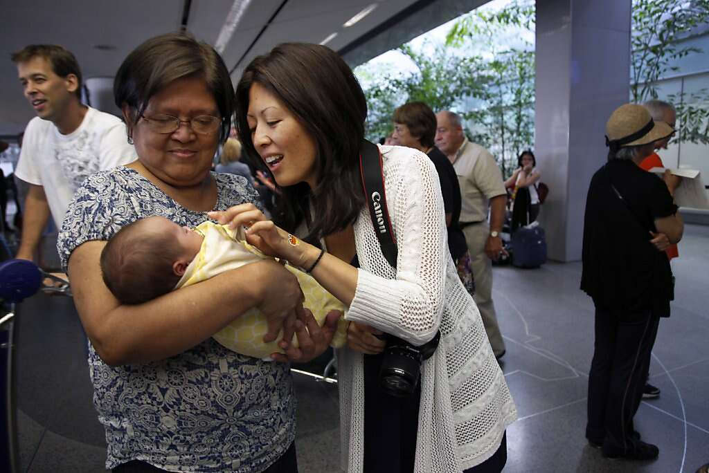 "Jennifer Benito-Kowalski's mother, Clemencia ""Amy"" Benito (left) and sister Lourdes Benito-Goodall meet baby Kyle for the first time at San Francisco International Airport, Saturday, June 15, 2013. Photo: Nicole Fruge, The Chronicle"