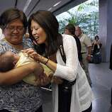 """Jennifer Benito-Kowalski's mother, Clemencia """"Amy"""" Benito (left) and sister Lourdes Benito-Goodall meet baby Kyle for the first time at San Francisco International Airport, Saturday, June 15, 2013."""