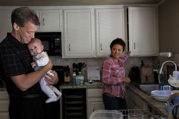 Steve Kowalski holds baby Kyle as wife Jennifer Benito-Kowalski puts away dishes in their home in San Carlos, Calif., Wednesday, August 7, 2013. Photo: Nicole Fruge, The Chronicle
