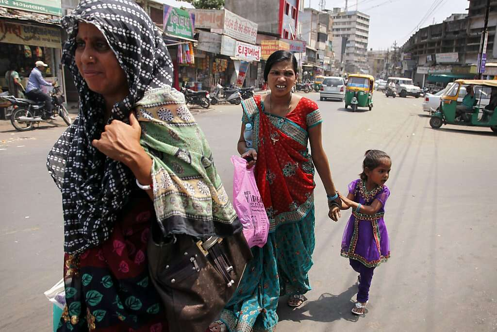 While still in pain from a cesarean section, Manisha Parmar and daughter Urvashi (right) walk through the streets in Anand, India, before catching a tuk-tuk ride back home to Khambhat, Monday, June 3, 2013. Usha Parmar, Raman's cousin who recruited Manisha into surrogacy, is in the foreground. Photo: Nicole Fruge, The Chronicle