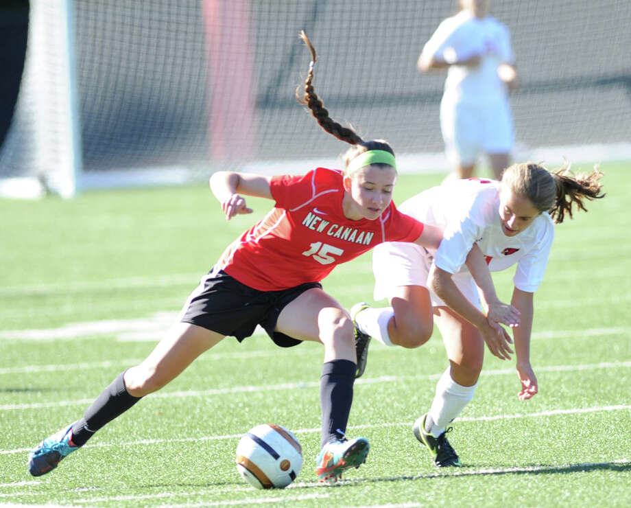 At left, Gabriella Borea (# 15) of New Canaan, gets tangled up with Emily Berzolla, right, of Greenwich, during the girls varsity soccer match between Greenwich High School and New Canaan High School at Greenwich, Tuesday, Sept. 17, 2013. New Canaan defeated Greenwich, 2-1. Photo: Bob Luckey / Greenwich Time