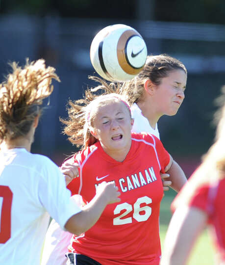 At center, Courtney Overacker (# 26) of New Canaan heads the ball between two Greenwich defenders du