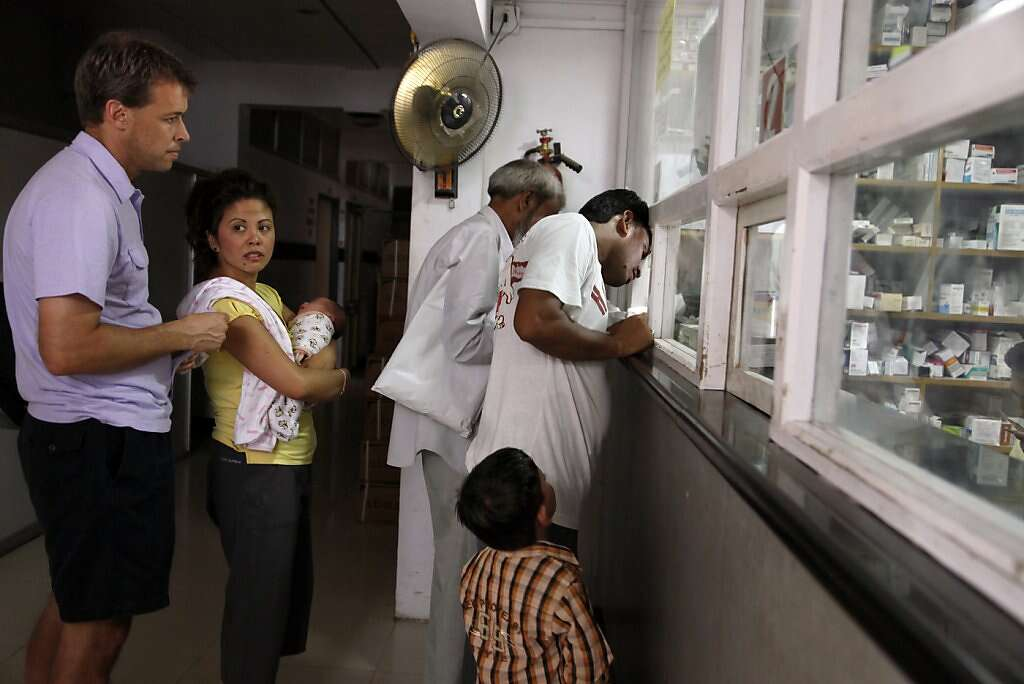 Steve Kowalski and Jennifer Benito-Kowalski take baby Kyle to pick up medication for his upcoming flights to Mumbai and the U.S. at the pharmacy in the Apara Nursing Home in Anand, India, Friday, May 31, 2013. Photo: Nicole Fruge, The Chronicle
