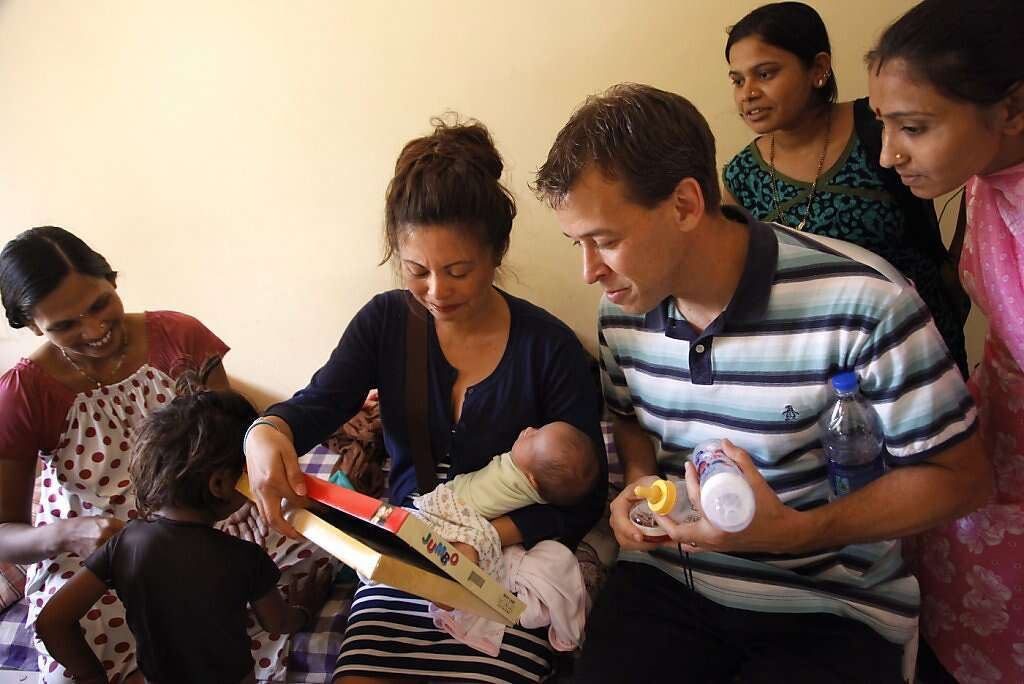 Jennifer Benito-Kowalski (center) and Steve Kowalski look at gifts for baby Kyle from surrogate Manisha Parmar (left) as two former surrogates look on at the Akanksha Infertility Clinic in Anand, India, Saturday, June 1, 2013. Parmar gave Kyle baby clothes and a tiny silver bracelet. The wristlet is a customary gift for newborns in India. Photo: Nicole Fruge, The Chronicle