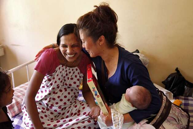 Jennifer Benito-Kowalski (right) is receives gifts for baby Kyle from surrogate Manisha Parmar at the Akanksha Infertility Clinic in Anand, India, Saturday, June 1, 2013. Parmar gave Kyle baby clothes and a tiny silver bracelet. The wristlet is a customary gift for newborns in India. Photo: Nicole Fruge, The Chronicle