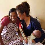 Jennifer Benito-Kowalski (right) is receives gifts for baby Kyle from surrogate Manisha Parmar at the Akanksha Infertility Clinic in Anand, India, Saturday, June 1, 2013. Parmar gave Kyle baby clothes and a tiny silver bracelet. The wristlet is a customary gift for newborns in India.