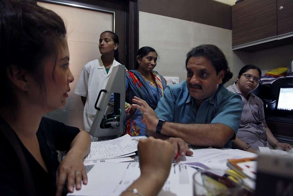Jennifer Benito-Kowalski, left, reviews the final bill with Dr. Hitesh Patel at the Akanksha Infertility Clinic in Anand, India, Thursday, May 30, 2013. At first  Dr. Patel, claimed that Benito-Kowalski still had a balance owed but late reversed himself and said the clinic owed the couple a refund. Photo: Nicole Fruge, The Chronicle