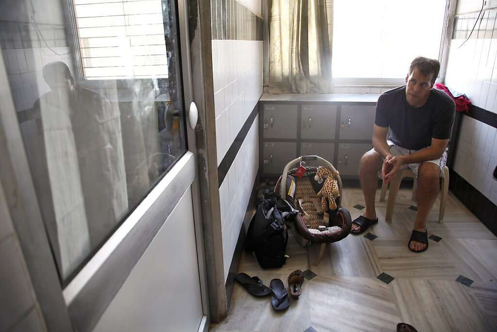 "After a nurse closed the curtains, Steve Kowalski waits for his wife Jennifer Benito-Kowalski and son Kyle Benito Kowalski to leave the nursery at the Apara Nursing Home in Anand, India, Friday, May 24, 2013. Kyle spent a night in the hospital before being released to his parents. Healthcare workers tended to Jennifer but often left Steve out. Baby Kyle's paperwork was even labelled ""Baby of Jennifer."" Photo: Nicole Fruge, The Chronicle"