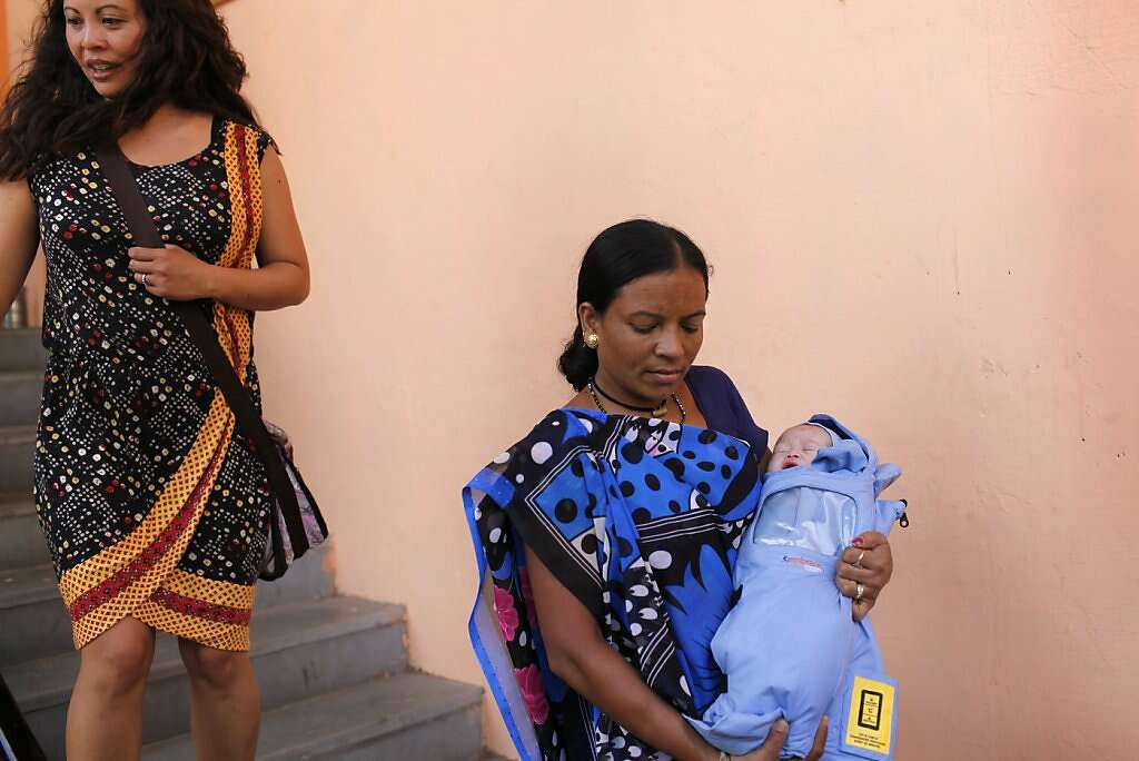 A pediatrician's helper, Tiupi Dave, carries baby Kyle Benito Kowalski down the operating room stairs to a waiting car as his mom Jennifer Benito-Kowalski follows behind at the Akanksha Infertility Clinic in Anand, India, Thursday, May 23, 2013. The car travelled two blocks to the Apara Nursing Home, a hospital whose facilities included a neonatal intensive care unit. The Kowalskis had no idea where the baby was being taken until they arrived. Photo: Nicole Fruge, The Chronicle