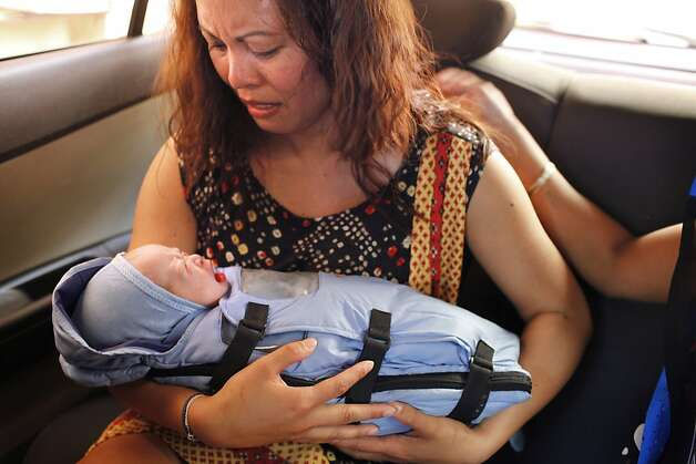 Jennifer Benito-Kowalski holds her son baby Kyle Benito Kowalski for the first extended time in a car outside the Akanksha Infertility Clinic in Anand, India, Thursday, May 23, 2013. The car travelled two blocks to the Apara Nursing Home, a hospital whose facilities included a neonatal intensive care unit. The Kowalskis had no idea where the baby was being taken until they arrived. Photo: Nicole Fruge, The Chronicle