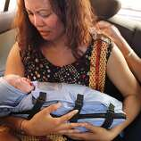 Jennifer Benito-Kowalski holds her son baby Kyle Benito Kowalski for the first extended time in a car outside the Akanksha Infertility Clinic in Anand, India, Thursday, May 23, 2013. The car travelled two blocks to the Apara Nursing Home, a hospital whose facilities included a neonatal intensive care unit. The Kowalskis had no idea where the baby was being taken until they arrived.