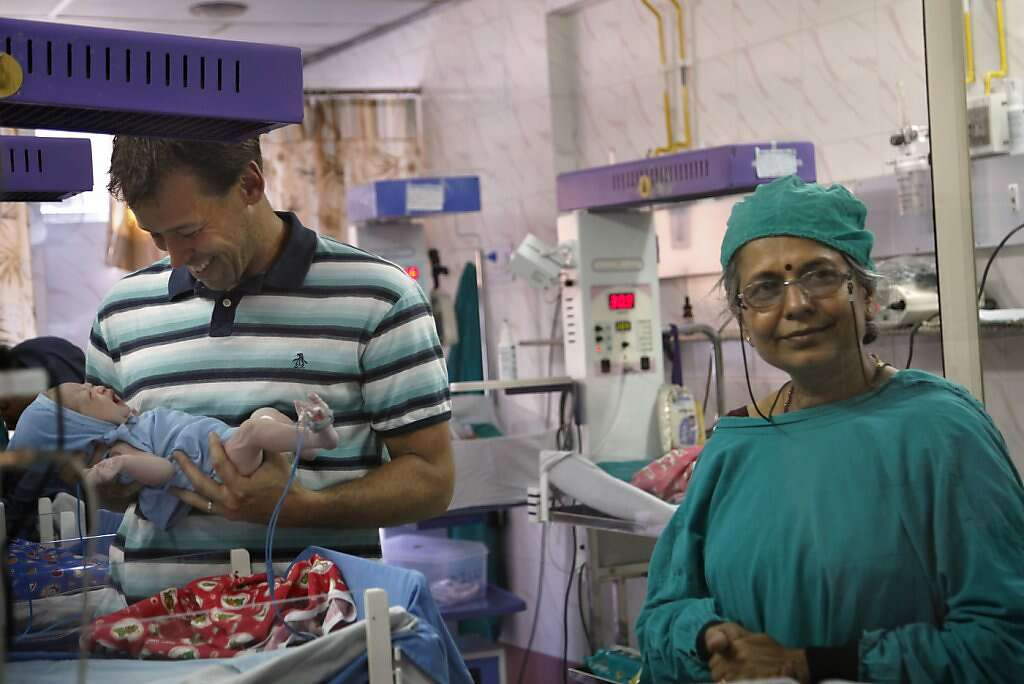 Steve Kowalski holds his son Kyle Benito Kowalski for the first time in the nursery at the Apara Nursing Home in Anand, India, Thursday, May 23, 2013. Kyle was born a healthy 7 pounds, 2 ounces. Pediatrician Dr. Anita Kothiala is on the right. Photo: Nicole Fruge, The Chronicle