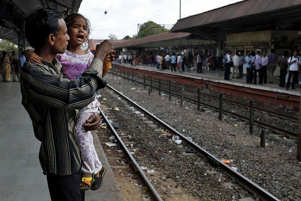 Raman Parmar and his daughter, Urvashi, 3, wait for the train in Anand, India, Saturday, May 25, 2013. Raman returned home to Khambhat to work on renovating his house before Manisha's release from the hospital. Raman struggled to juggle child care and his work as a day laborer while his wife was away. Photo: Nicole Fruge, The Chronicle