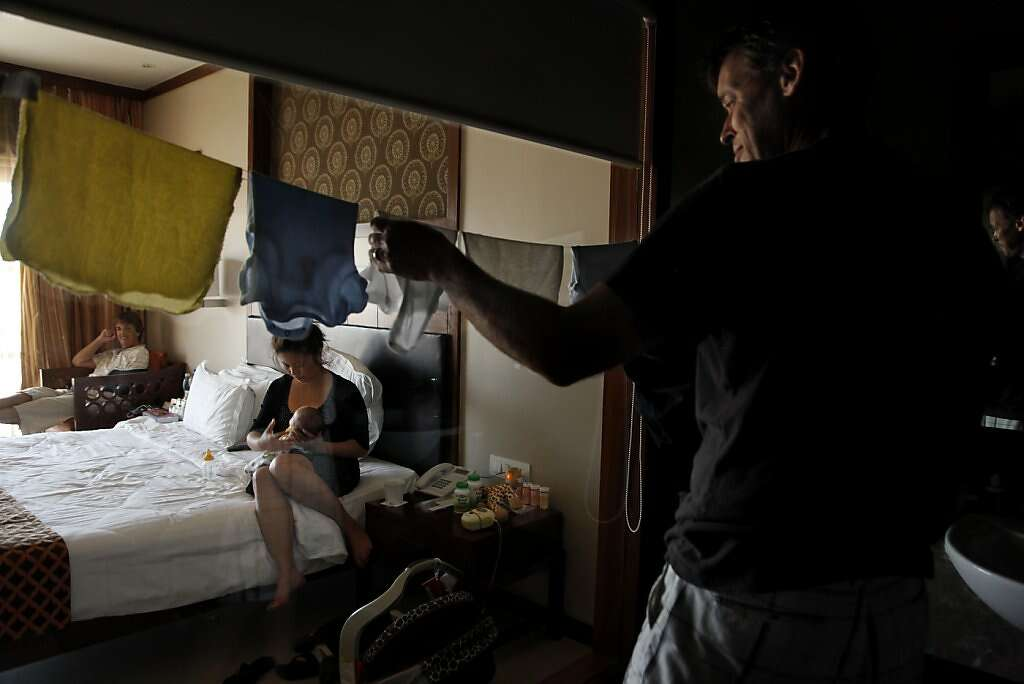 Steve Kowalski hangs laundry in his hotel room at the Madhubhan Resort and Spa, as his wife Jennifer and mom Sue look on, in Anand, India, Thursday, May 30, 2013. Steve and Jennifer were beginning to miss the confronts of home, particularly their washer and dryer. Photo: Nicole Fruge, The Chronicle