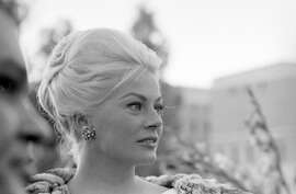 Anita Ekberg wearing gold earings encrusted with sapphires and diamonds at the Boccaccio 70 premiere in Rome, 1961.