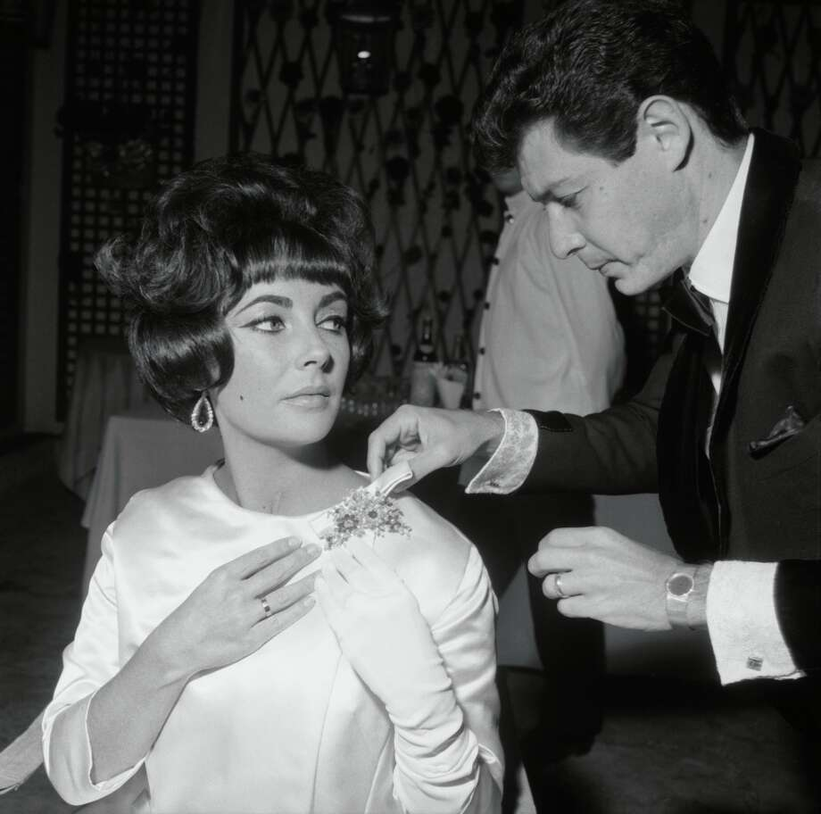 """Singer Eddie Fisher adjusts a brooch on the shoulder of Elizabeth Taylor at  a party she gave to celebrate Kirk Douglas' film """"Spartacus"""" at Rome's Grand Hotel in 1961. Photo: Courtesy Of The De Young And Bulgari"""