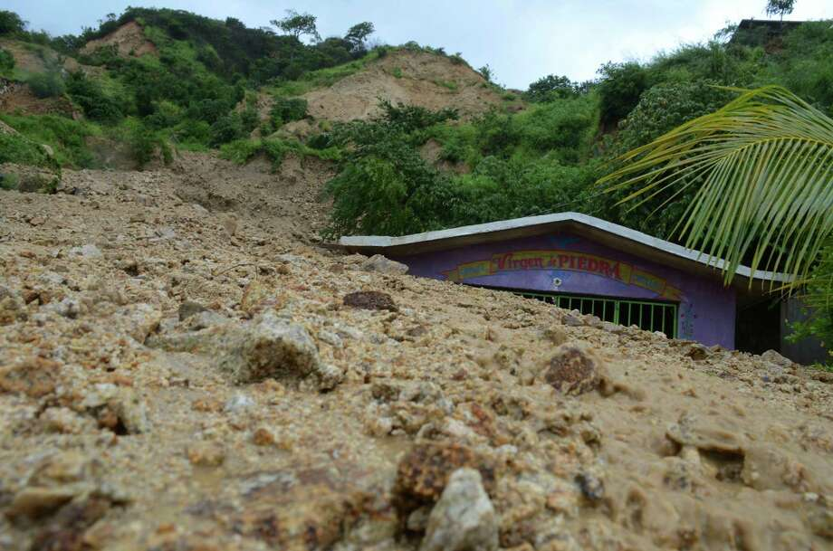 A small chapel is engulfed in rock and mud from a landslide triggered by heavy rains brought on by Tropical Storm Manuel on the outskirts of Acapulco, Mexico, Monday, Sept. 16, 2013. Tropical Storm Ingrid and remnants of Tropical Storm Manuel drenched Mexico's Gulf and Pacific coasts, flooding towns and cities in a national emergency that federal authorities say has caused at least 34 deaths. (AP Photo/Bernandino Hernandez) Photo: Bernandino Hernandez, STR / AP