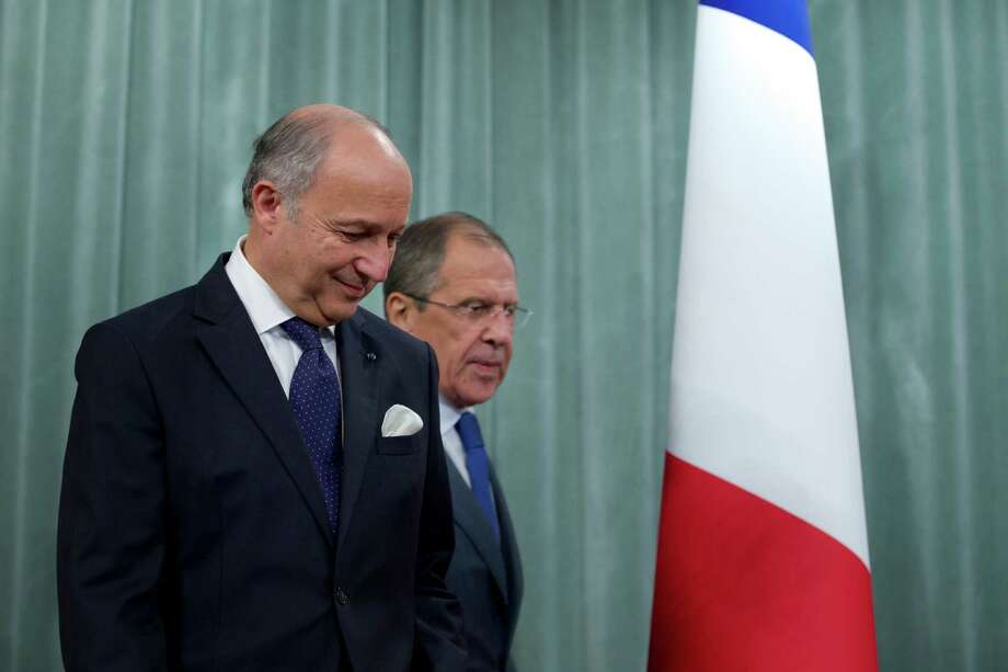 French Foreign Minister Laurent Fabius, left, and his Russian counterpart Sergey Lavrov arrive for a news conference after their meeting in Moscow, Russia, on Tuesday, Sept. 17, 2013. Moscow is insisting that a new United Nations resolution on Syria not allow the use of force, but Russia's foreign minister appears to suggest the issue could be reconsidered if Syria violates an agreement on abandoning its chemical weapons. (AP Photo/Ivan Sekretarev) Photo: Ivan Sekretarev, STF / AP
