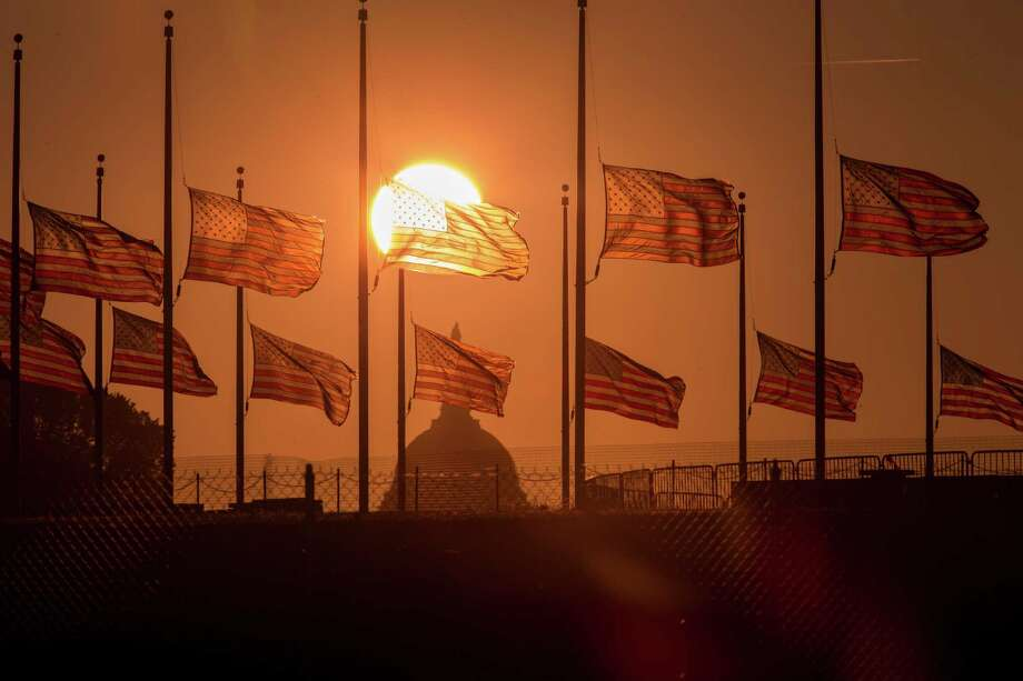 The flags at the Washington Monument fly at half-staff on Tuesday. The Navy Yard killer was not in an FBI system monitoring felons or mentally ill people. Photo: J. Scott Applewhite, STF / AP
