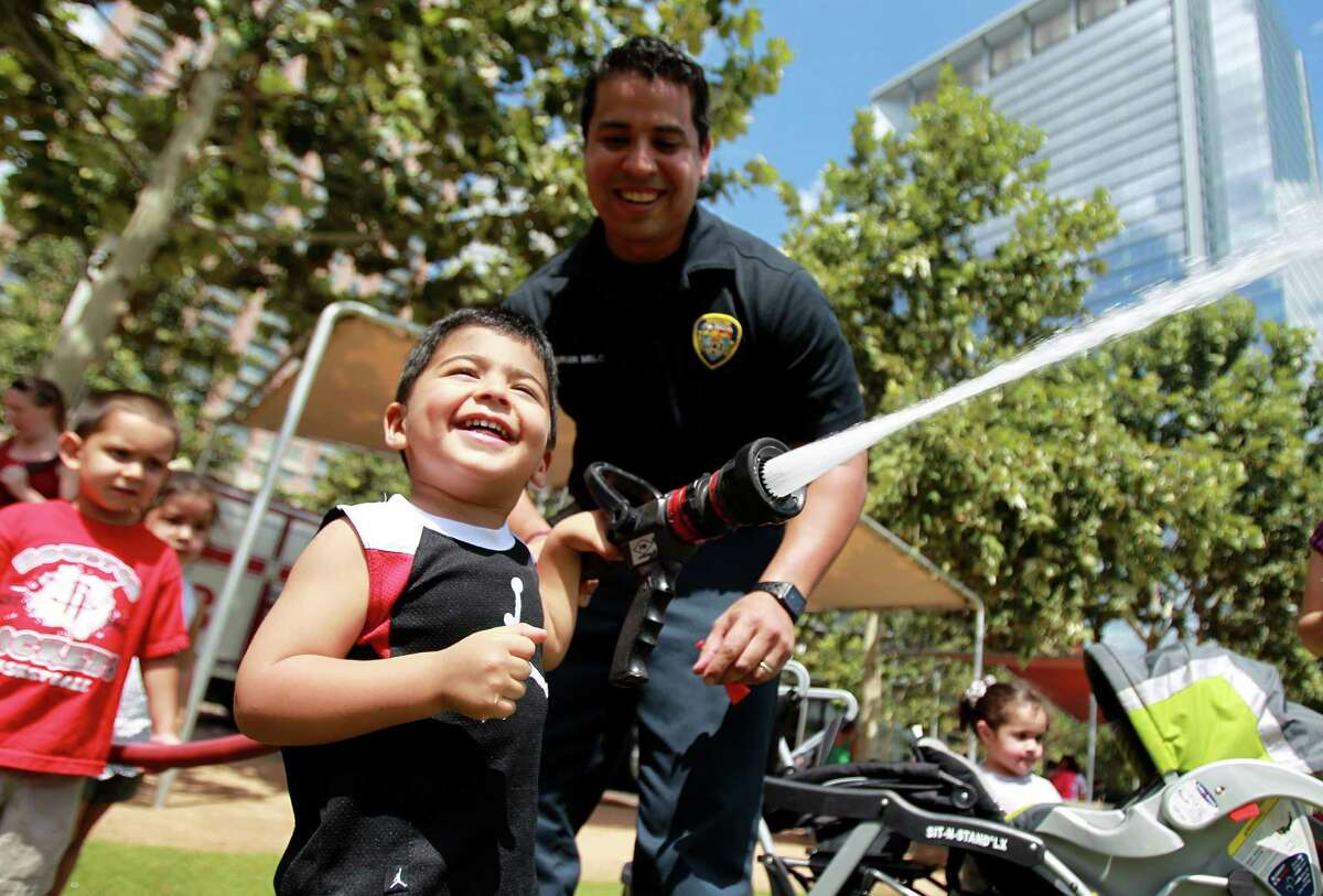 """Houston Fire Department firefighter Adrian Melchor assists D.R. Rashid, 2, with the water hose after listening to the story, """"Barney: Let's Go to the Firehouse,"""" during Toddler Tuesday at Discovery Green on Tuesday, Sept. 17, 2013, in Houston."""
