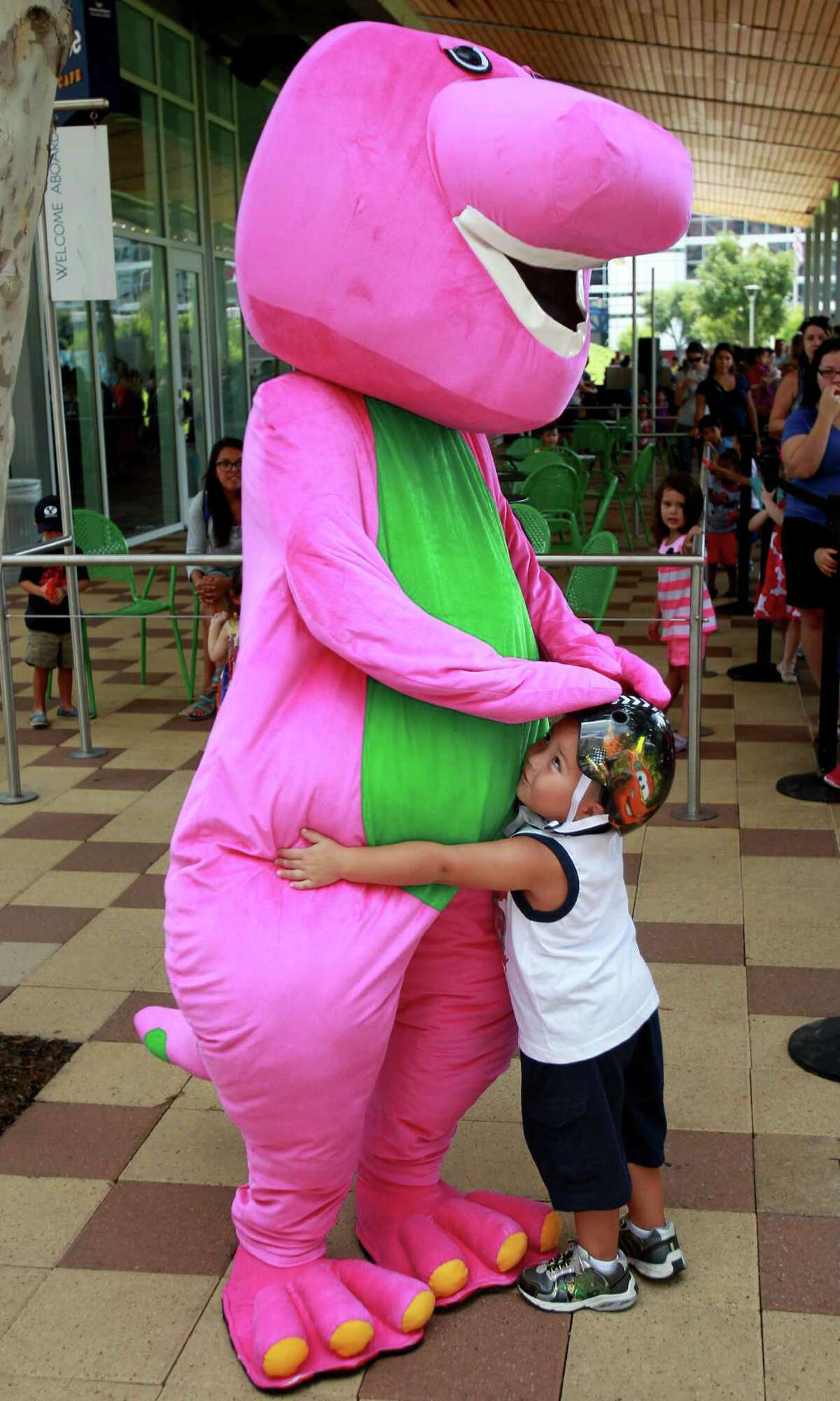 """Elijah Morales, 3, hugs Barney after listening to the story, """"Barney: Let's Go to the Firehouse,"""" during Toddler Tuesday at Discovery Green on Tuesday, Sept. 17, 2013, in Houston."""