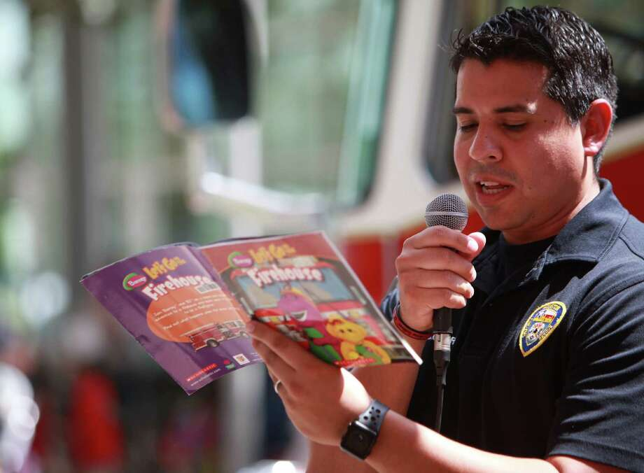 "HFD firefighter Adrian Melchor reads ""Barney: Let's Go to the Firehouse"" for the second wave of visitors during Toddler Tuesday at Discovery Green on Tuesday, Sept. 17, 2013, in Houston. Photo: Mayra Beltran, Houston Chronicle / © 2013 Houston Chronicle"
