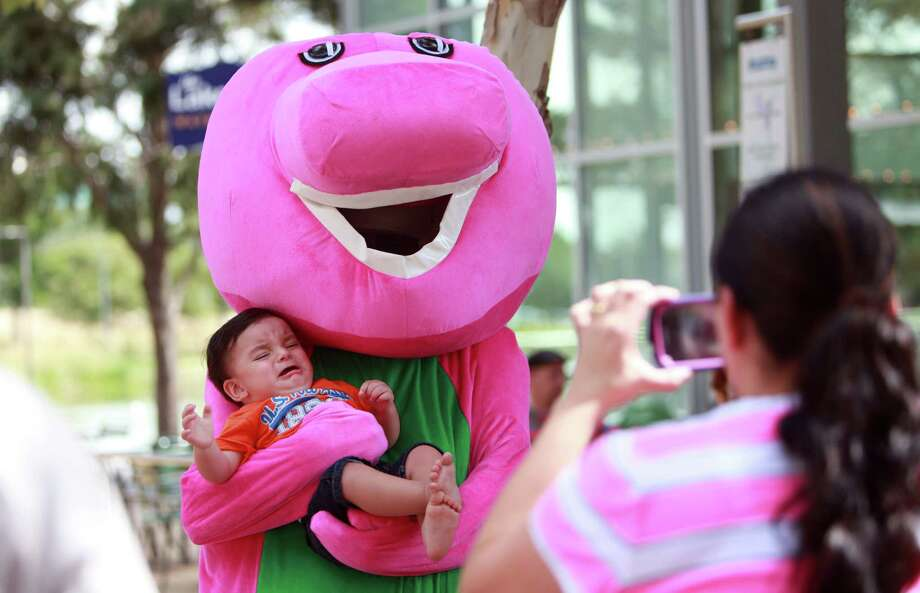 Rosy Cordova takes a photo of son Christopher Cordova, 1, with Barney. Photo: Mayra Beltran, Houston Chronicle / © 2013 Houston Chronicle