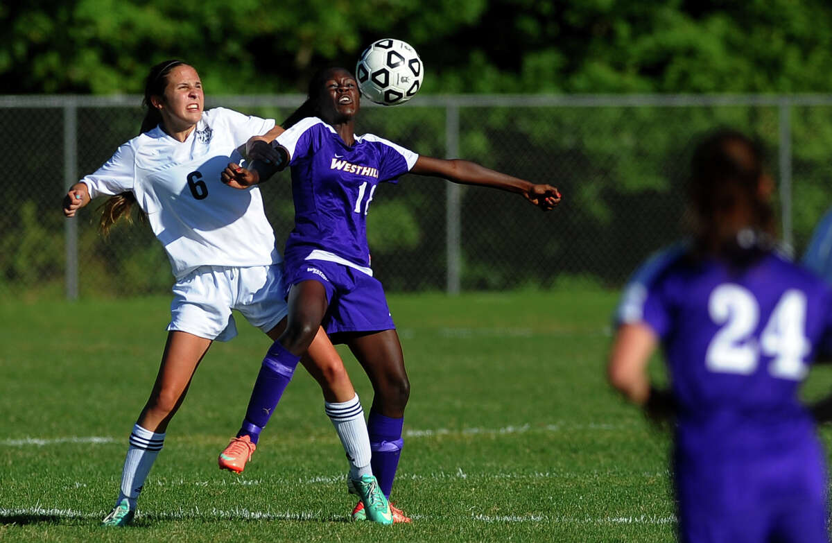 Trumbull's Kyriaki Marinos, left, and Westhill's Chelsea Domond, try to intercept the ball, during girls soccer action in Trumbull, Conn. on Tuesday September 17, 2013.
