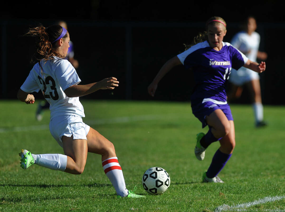 Trumbull's Lauren Hyde, left, prepares to kick a goal shot as Westhill's Claire Mioline rushes in to block, during girls soccer action in Trumbull, Conn. on Tuesday September 17, 2013. Hyde got the ball past the goalie to score.