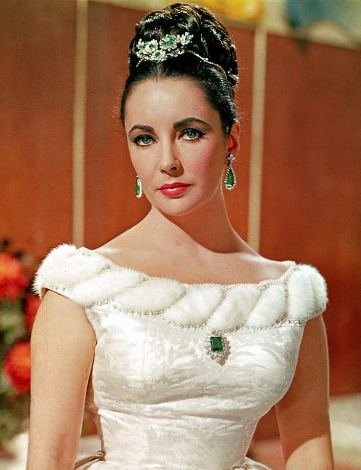 Elizabeth Taylor wearing a diamond brooch with a 23.44 octagonal step-cut emerald and matching earrings in ''The V.I.P.s'' (1963).  Richard Burton gave the brooch to Taylor upon their engagement in 1962. Photo: Courtesy Of The De Young And Bulgari