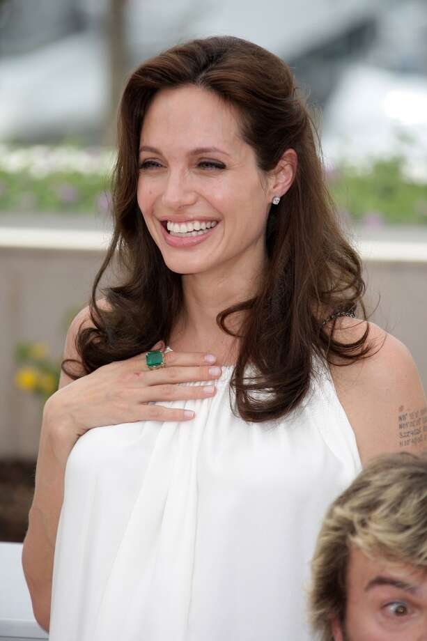 """Angelina Jolie wearing a yellow gold ring set with an emerald and diamonds from the 1992 Vintage Collection at the """"Kung Fu Panda"""" photocall during the Cannes International Film Festival in 2008. Photo: Daniele Venturelli, Courtesy Of The De Young And Bulgari"""