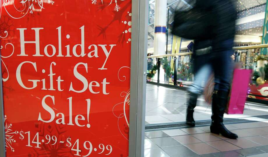 FILE - In this Monday, Dec. 24, 2012, file photo, a retail store at the CambridgeSide Galleria mall in Cambridge, Mass., advertises  holiday sale. Coming off of a weak back-to-school shopping period, a research firm said Thursday, Sept. 17, 2013, that holiday sales growth will be slower this year during the crucial holiday season. Shoppers are also expected to visit fewer stores as they research purchases online.   (AP Photo/Michael Dwyer, File) Photo: Michael Dwyer, STF / AP