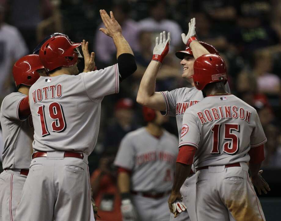 Jay Bruce of the Reds is congratulated by teammates after hitting a grand slam against the Astros. Photo: Melissa Phillip, Houston Chronicle
